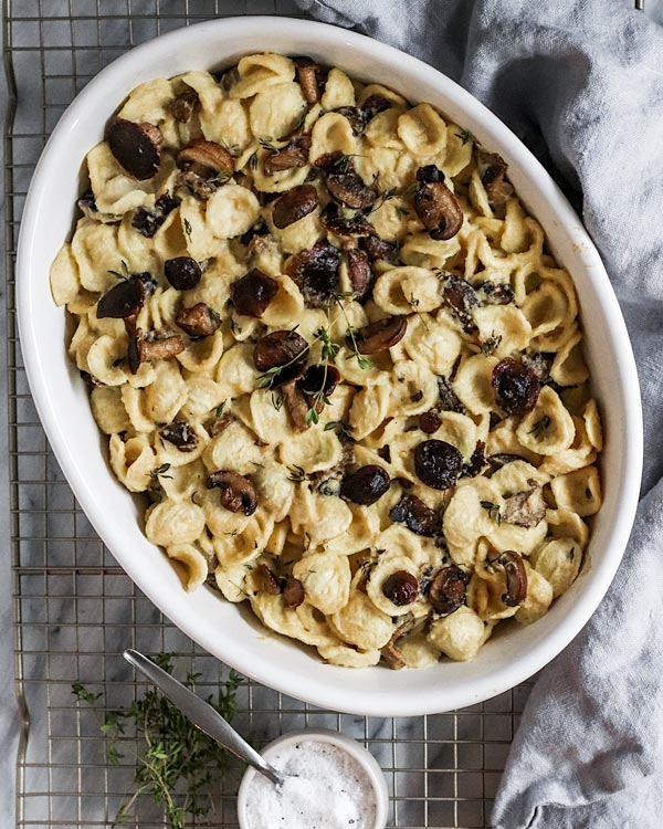 an oval baking dish filled with orecchiette pasta, mushrooms, thyme, and a cream sauce