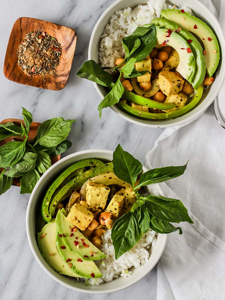 two bowls of thai basil green curry with tofu, avocado, and chickpeas