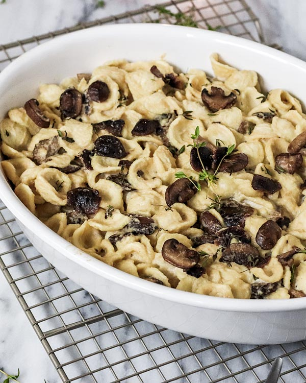 A casserole dish filled with pasta and mushrooms covered in a vegan truffle mushroom sauce