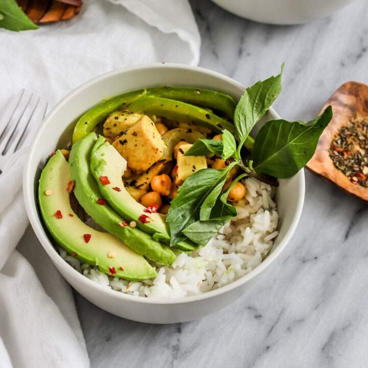 a bowl of thai basil coconut curry with tofu, avocado, and chickpeas