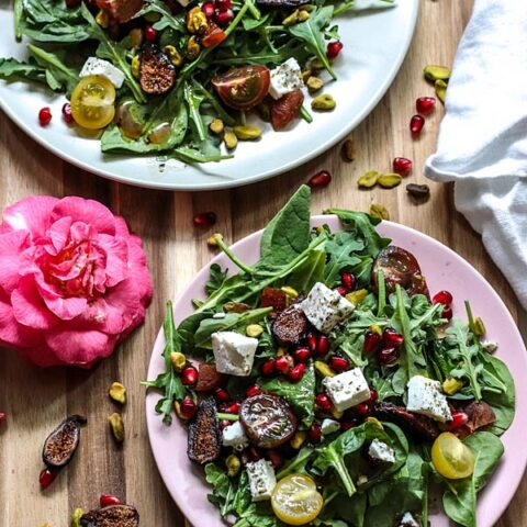 Two salad plates filled with lettuce, feta, cherry tomatoes, dried figs, salted pistachios, pomegranate seeds, and pomegranate dressing