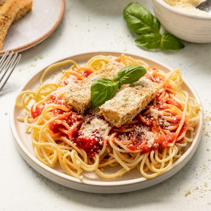 plate with pasta, tomato sauce, tofu parmesan, and basil