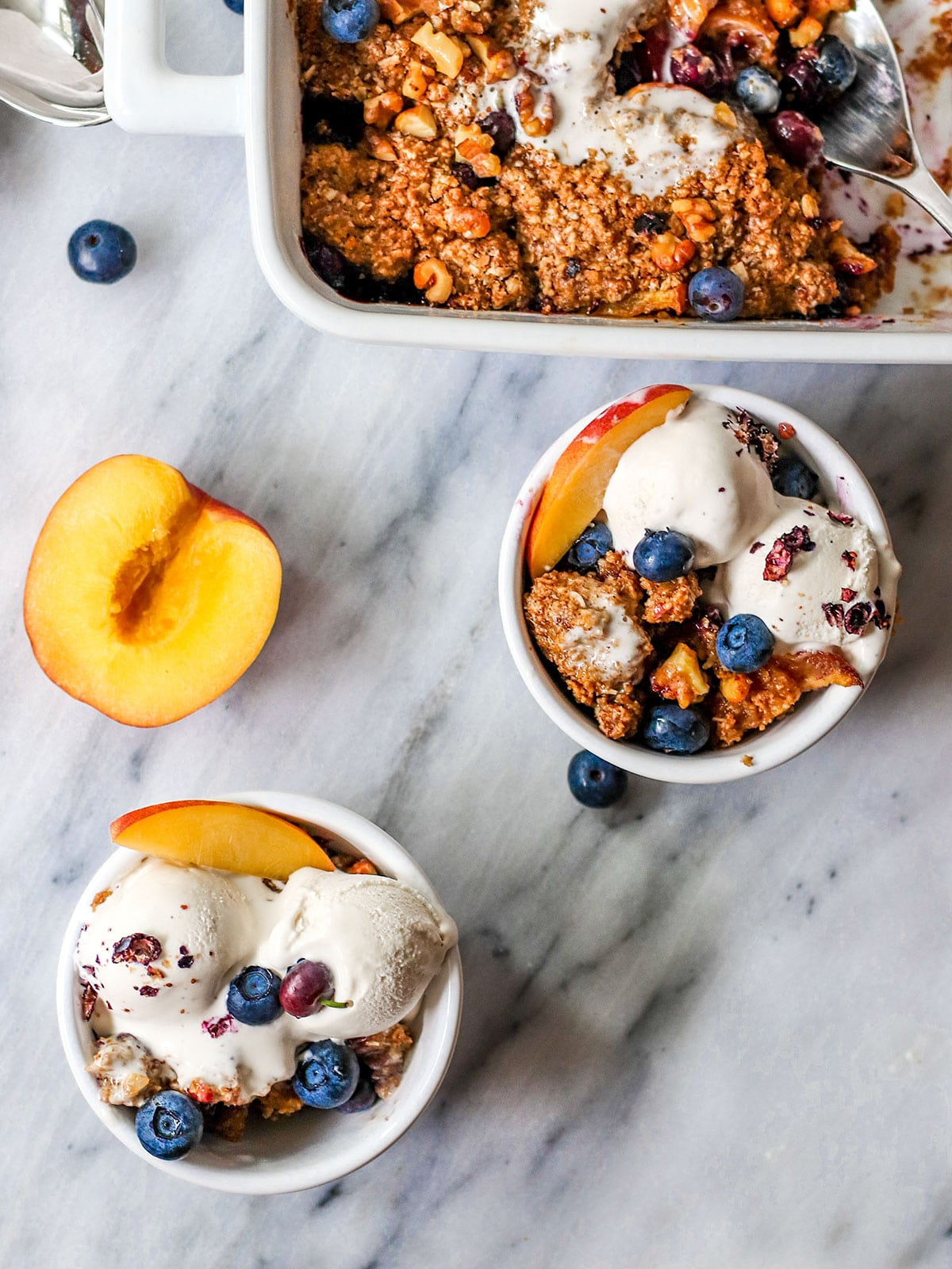 two bowls filled with nectarine blueberry crisp and ice cream