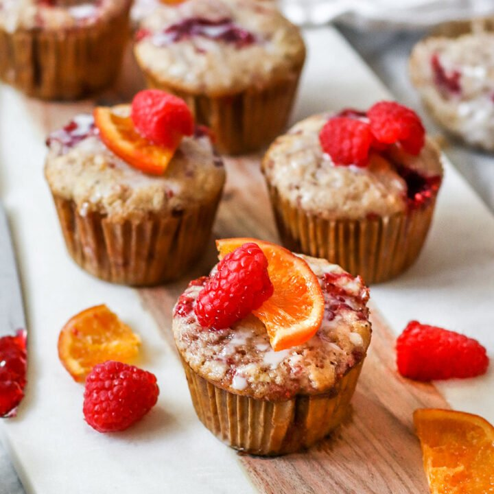 a tray of muffins with raspberry jam inside and orange slices and fresh raspberries on top