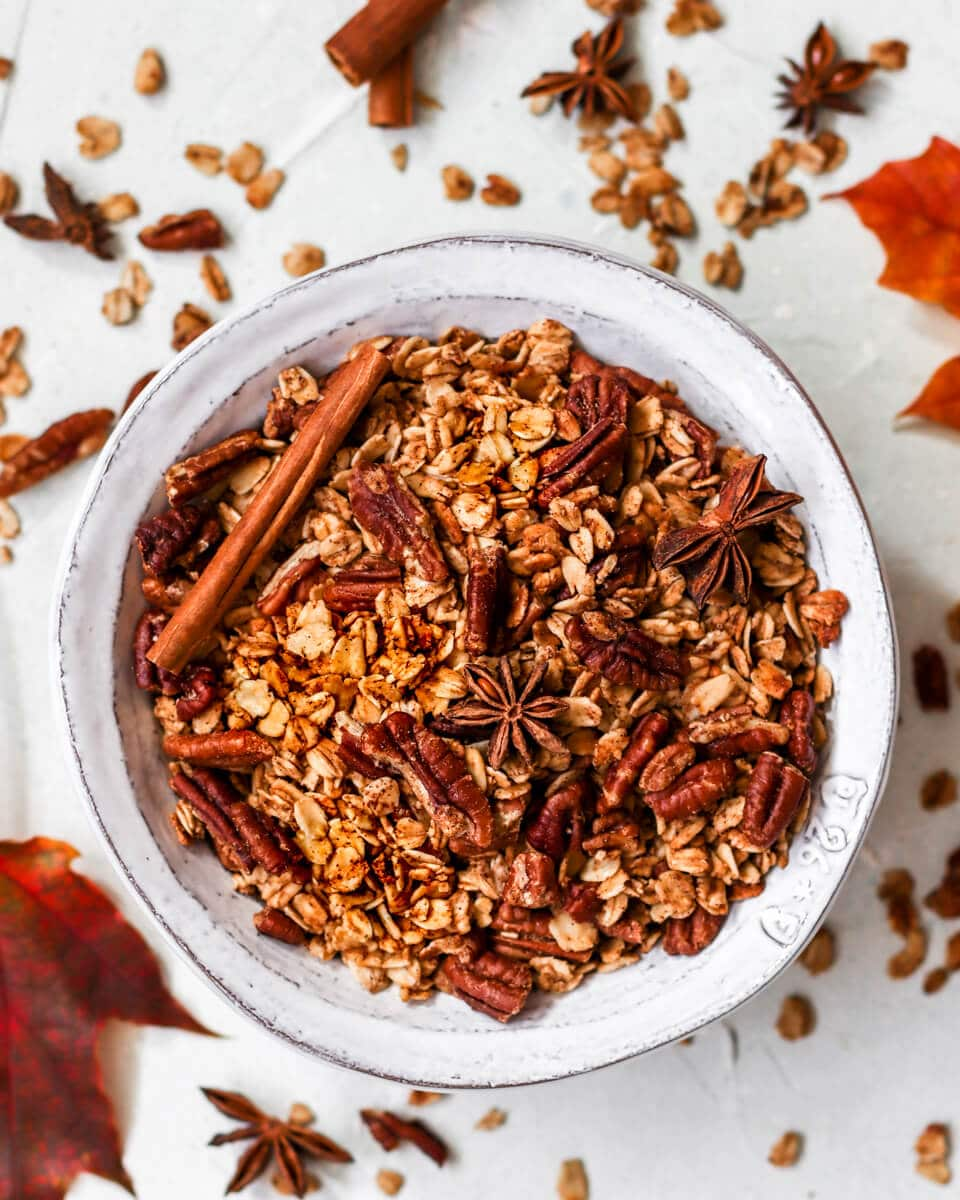a bowl of granola with oats, star anise, cinnamon, pecans, and spices