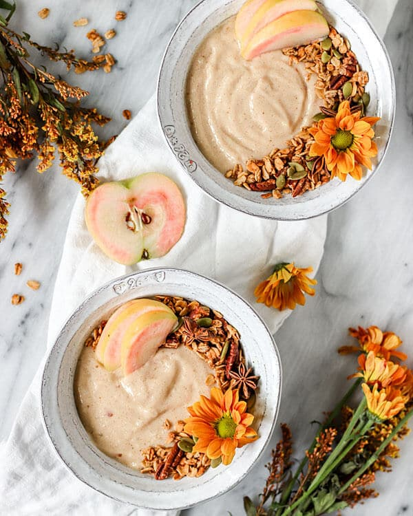 Two bowls filled with chai smoothies, chai pecan granola, and pink apples