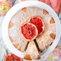 Grapefruit Olive Oil Cake with a slice cut out on top of a cake stand with grapefruit glaze and dried grapefruits on top