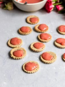 Vegan Linzer cookies getting topped with blood orange curd