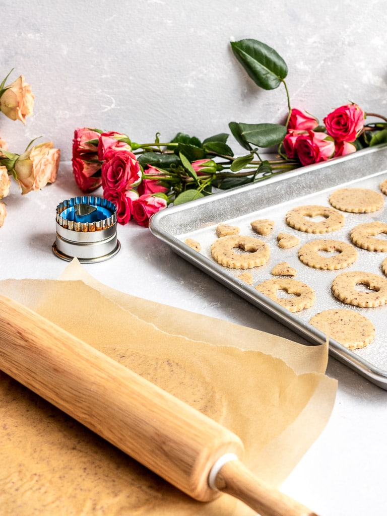 A rolling pin rolling out linzer cookies with cut out cookies on baking tray