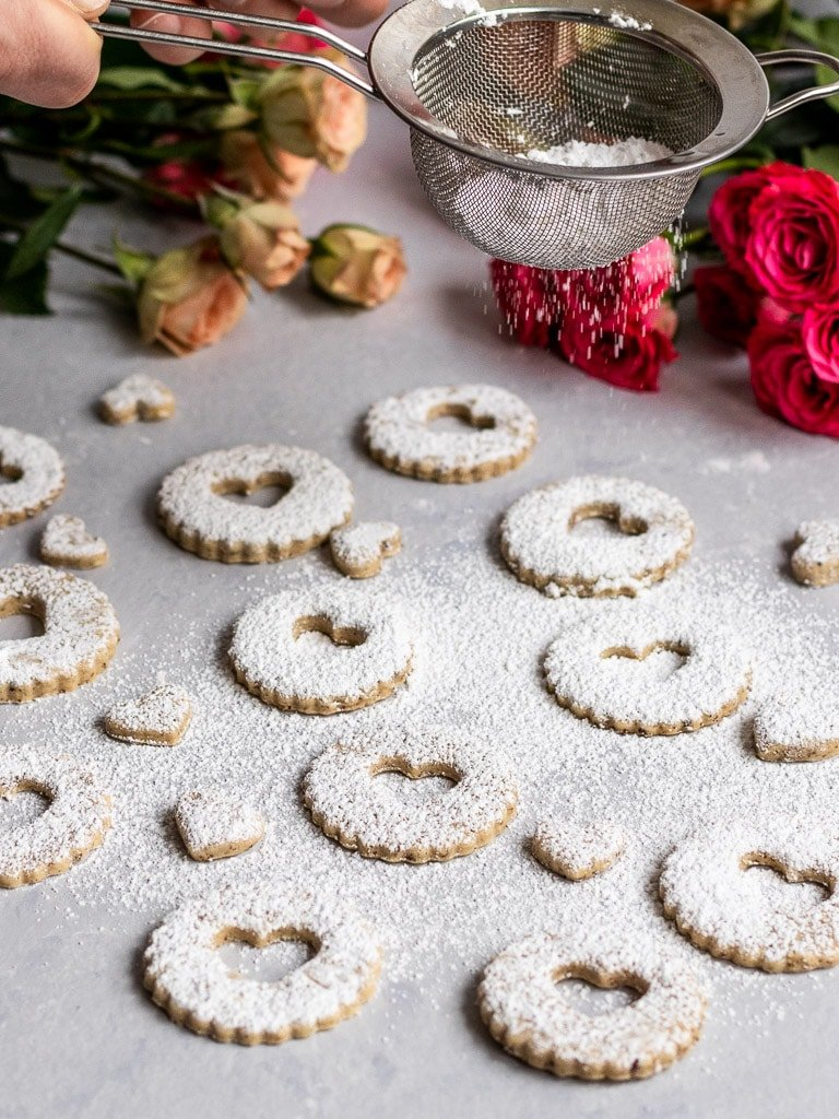Linzer cookies getting dusted with powdered sugar