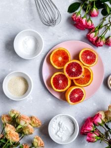 Blood orange on a plate surrounded by curd ingredients like arrowroot powder, sugar, and coconut cream