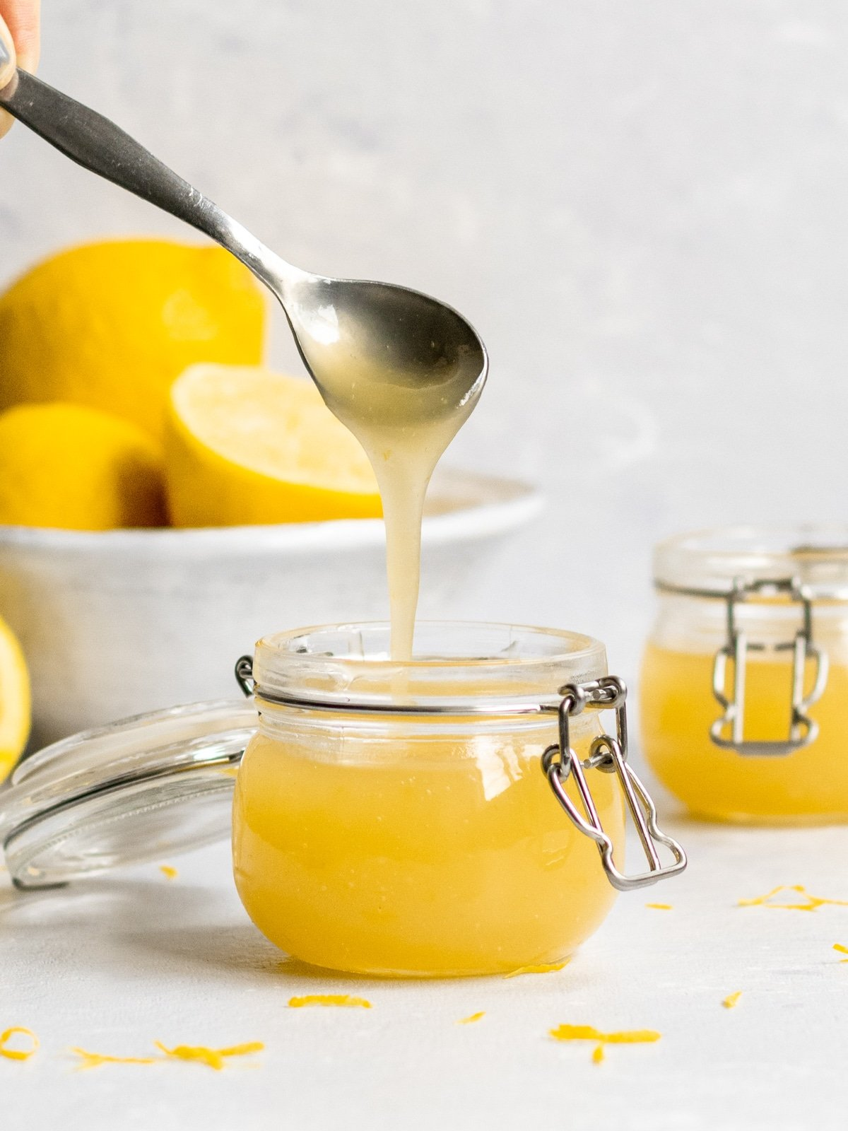 lemon curd in a container being drizzled out with a spoon