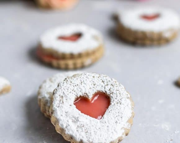 Heart shaped linzer cookies stuffed with pink blood orange curd surrounded by roses