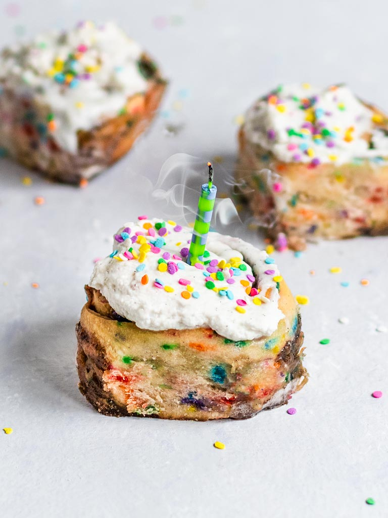 three funfetti cinnamon rolls with coconut frosting and a candle being blown out