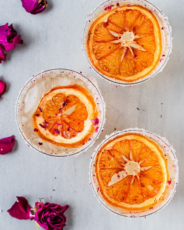 Three grapefruit rose paloma cocktails with dried grapefruit slices on top and a rose sugar rim