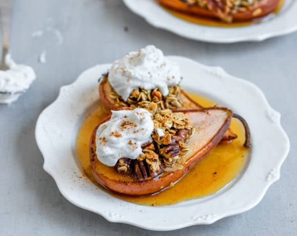 Two plates topped with 2 baked pears stuffed with maple oats and topped with coconut whipped cream and cinnamon