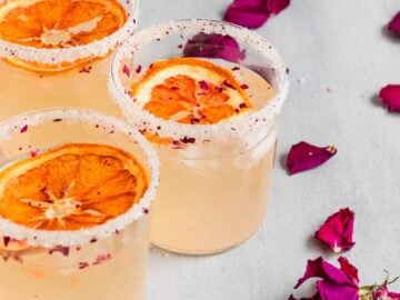 three cocktails topped with rose petals and dried grapefruit slices