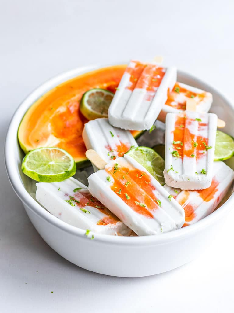 a bowl filled with coconut lime and papaya popsicles with lime slices