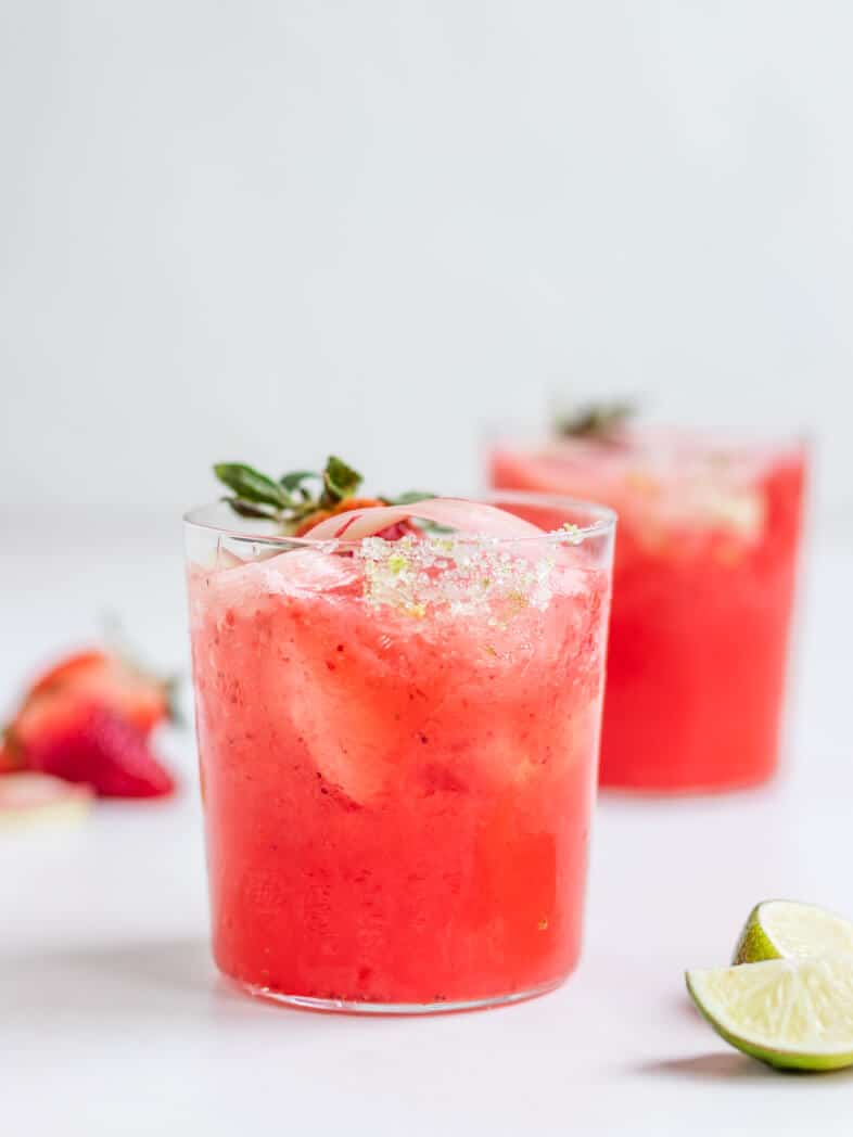 two glasses of frozen strawberry rhubarb margaritas with lime