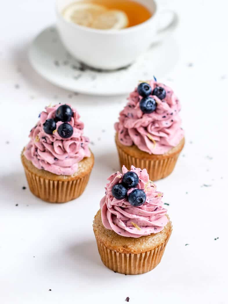 Three Earl Grey Cupcakes Topped with Swirls of Blueberry Lemon Frosting and Fresh Blueberries beside a cup of earl grey lemon tea