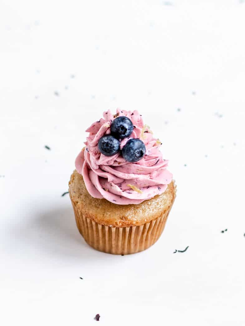 A Vegan Earl Grey Cupcake Topped with Swirls of Blueberry Lemon Frosting and Fresh Blueberries
