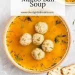 A bowl of matzo ball soup with fresh herbs and vegetables and matzah on the side