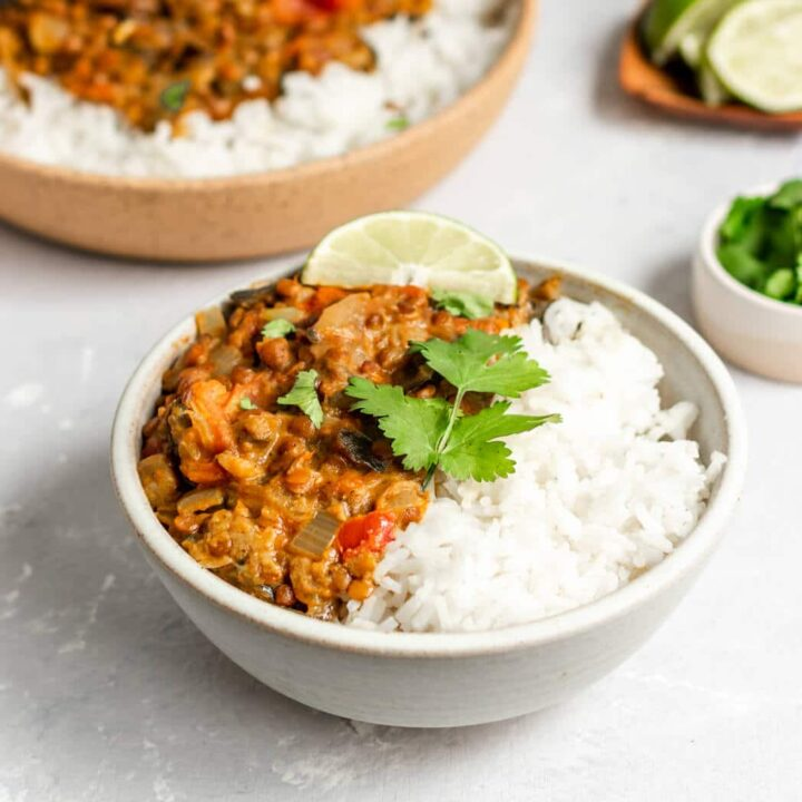 A bowl of vegan lentil eggplant curry over white rice topped with cilantro and fresh lime wedges