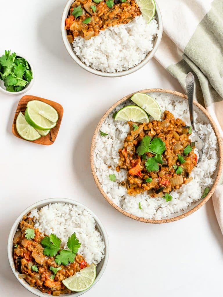 three bowls of eggplant lentil curry over white rice and topped with cilantro and lime wedges
