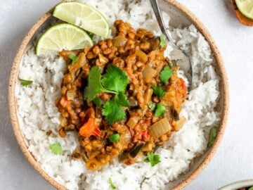 A bowl of vegan eggplant lentil curry over white rice and topped with cilantro and lime wedges