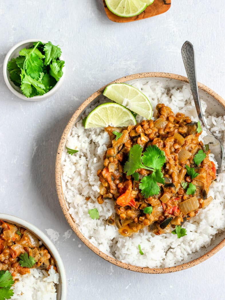 Vegan Eggplant and Lentil Curry on top of white rice with lime wedges and cilantro