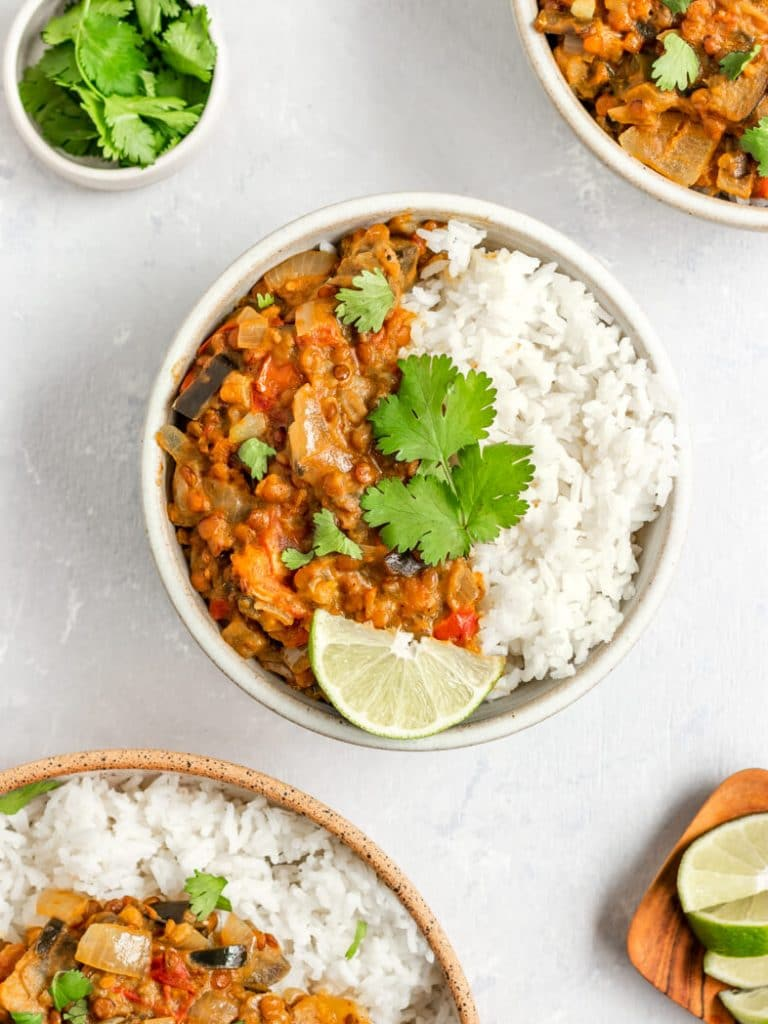 Bowls of Vegan Eggplant Lentil Curry over white rice and topped with cilantro and lime