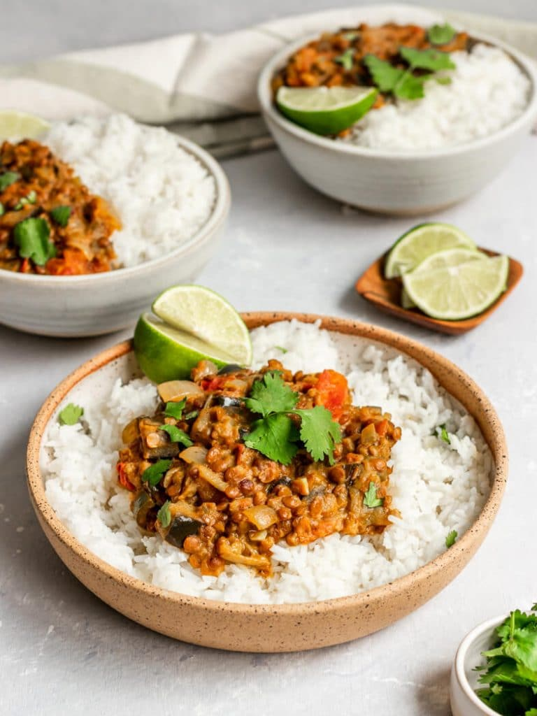 Three bowls of eggplant lentil curry over white rice topped with cilantro and fresh lime wedges