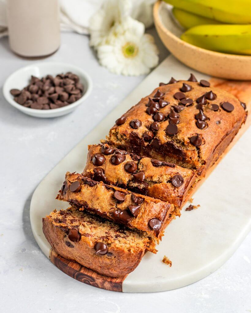 Vegan Tahini Banana Bread filed with chocolate chips and sliced alongside a large glass of almond milk