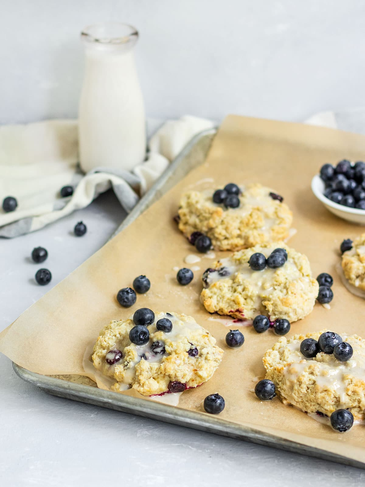 blueberry scones with fresh blueberries and vanilla glaze on a baking sheet