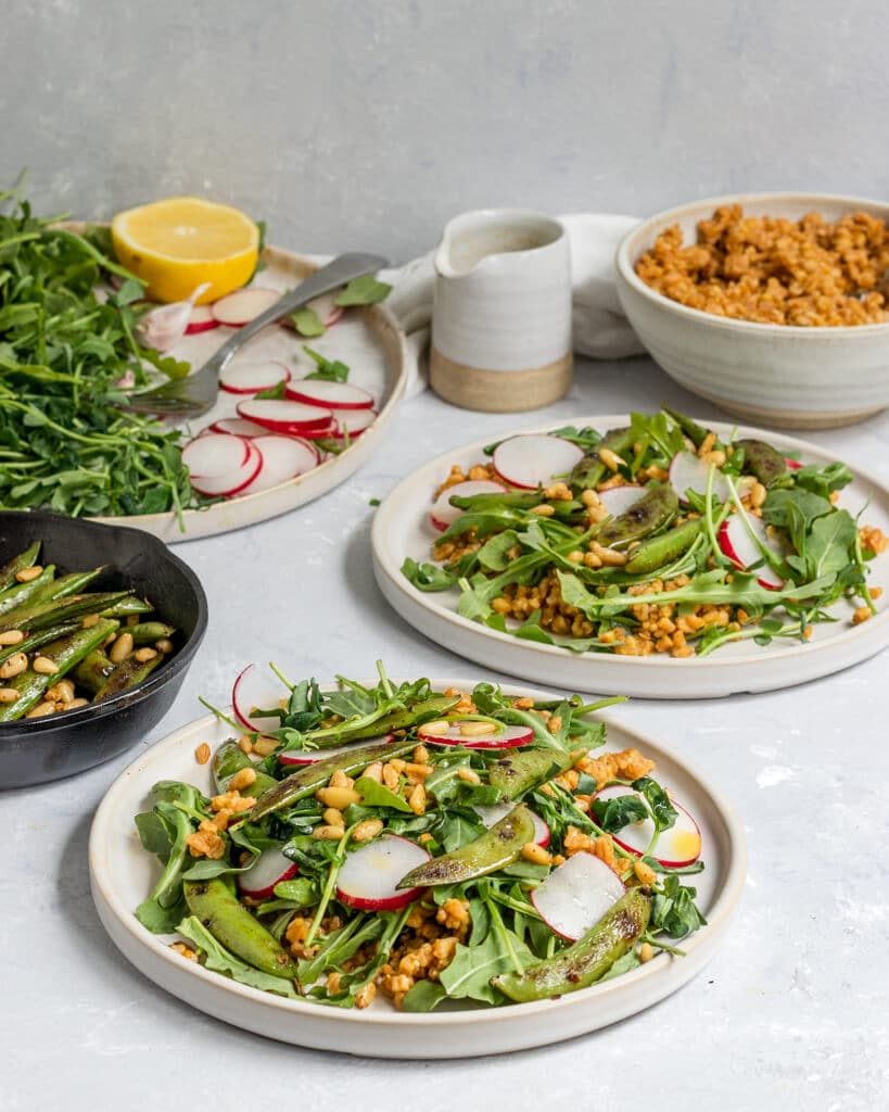 Two salad plates filled with arugula, grilled snap peas, farro, pine nuts, and radish slices alongside a container of lemon garlic dressing and extra salad ingredients