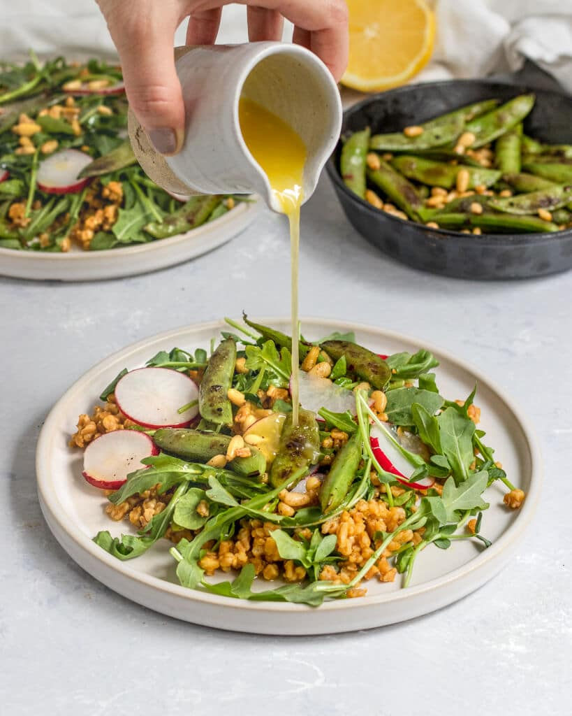 lemon dressing being poured onto a plate of salad with farro, arugula, snap peas,  radish