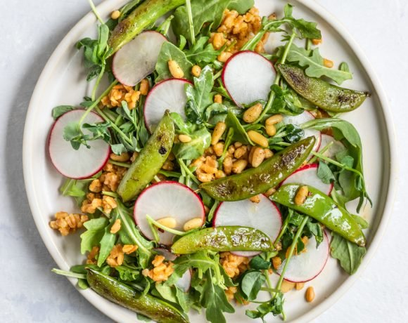 A plate filled with arugula, radish, farro, snap pea, pea shoot salad with lemon dressing