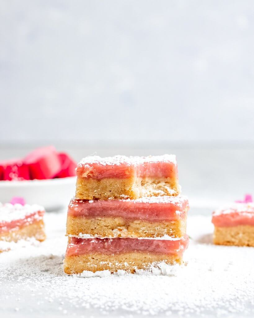 A Stack of Vegan Rhubarb Bars with a layer of vegan shortbread cookie and a layer of rhubarb curd. A bite is taken out to show the chewy smooth texture.