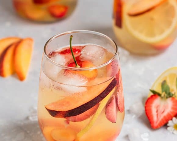 a glass of sangria filled with peaches, strawberries, lemon slices, rainier cherries, and ice