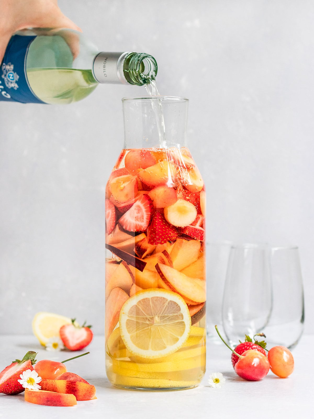 a pitcher filled with fresh lemon slices, peach slices, strawberries, and cherries getting filled with white wine