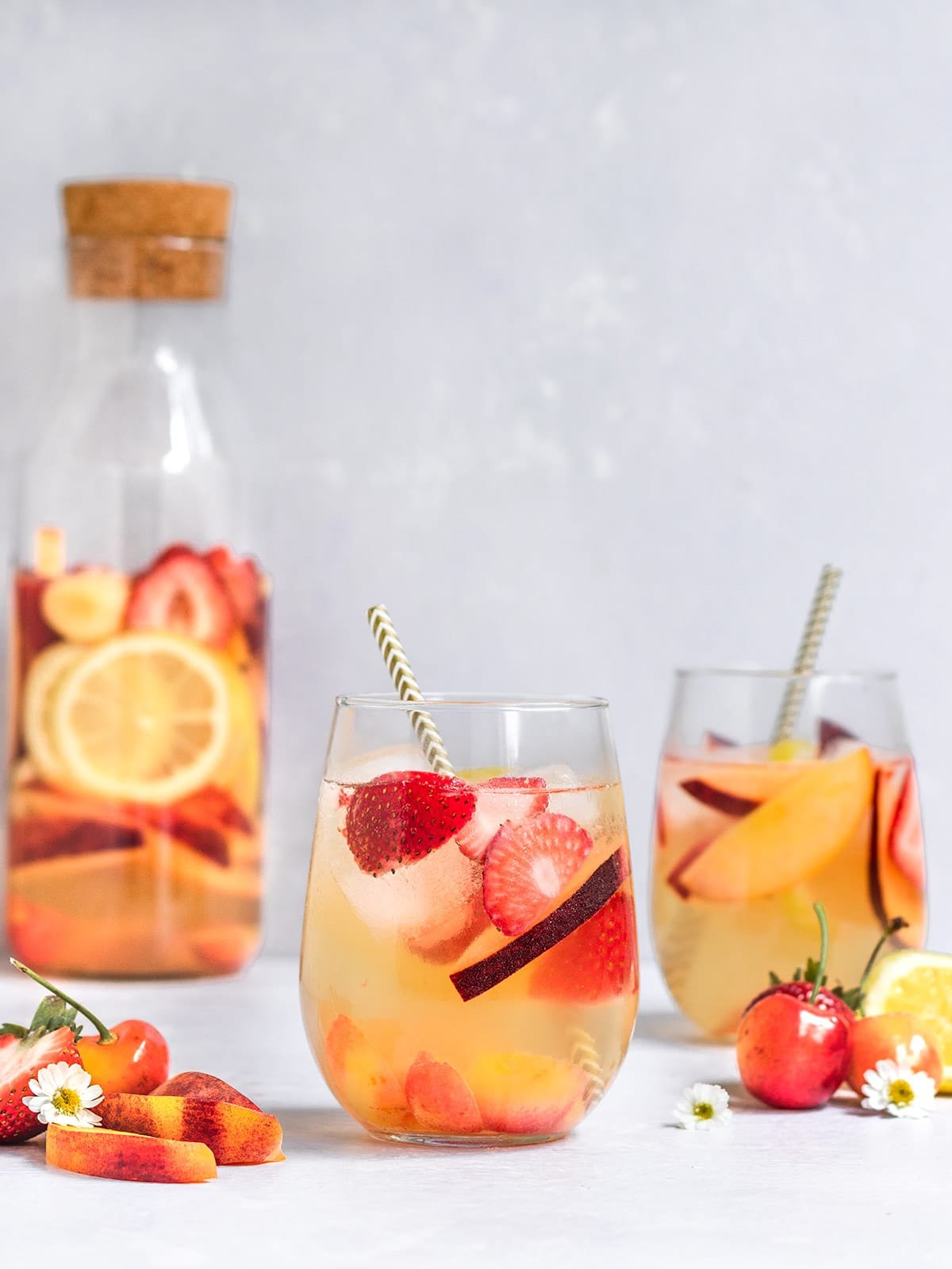 two glasses and a pitcher filled with white wine sangria, cherries, strawberries, peach slices, and lemon slices