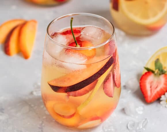 two glasses of sangria with fresh cherries, peach slices, lemon slices, and strawberries