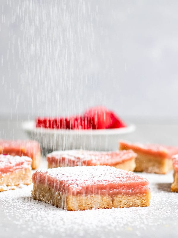 a vegan shortbread cookie bar topped with rhubarb curd being topped with powdered sugar