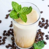 Homemade Iced Mint Latte In a glass topped with fresh mint surrounded by espresso beans