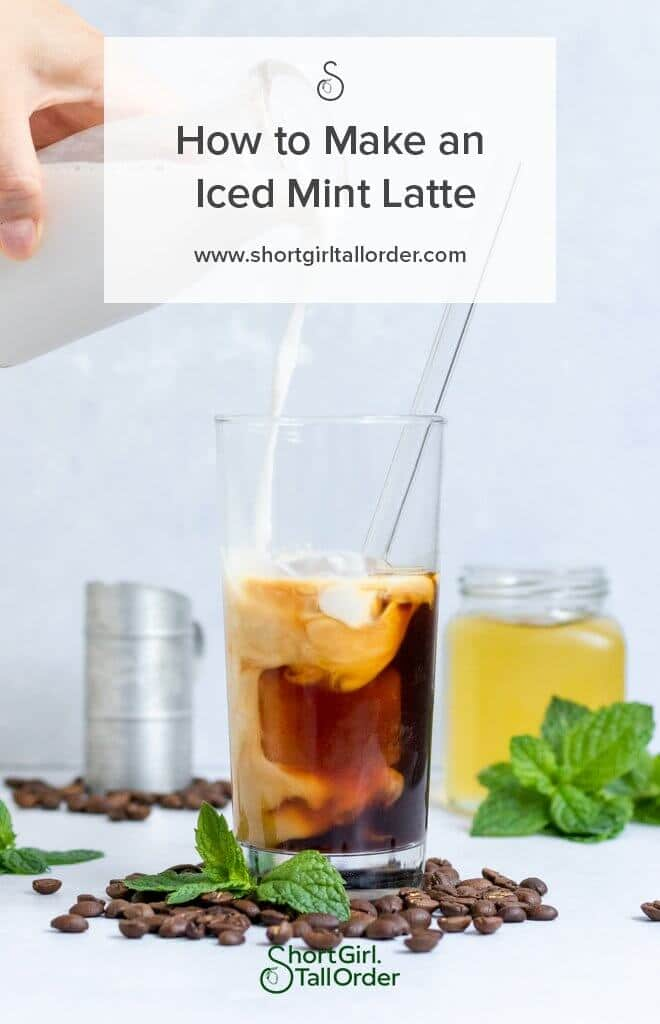 An Iced Mint Latte with milk being poured in surrounded by espresso beans and extra mint simple syrup