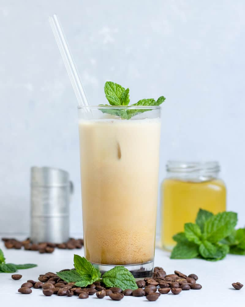An Iced Mint Latte surrounded by espresso beans and extra mint simple syrup