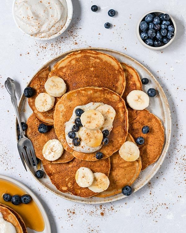 Layers of Vegan Banana Pancakes on a plate topped with coconut cream, bananas, and blueberries