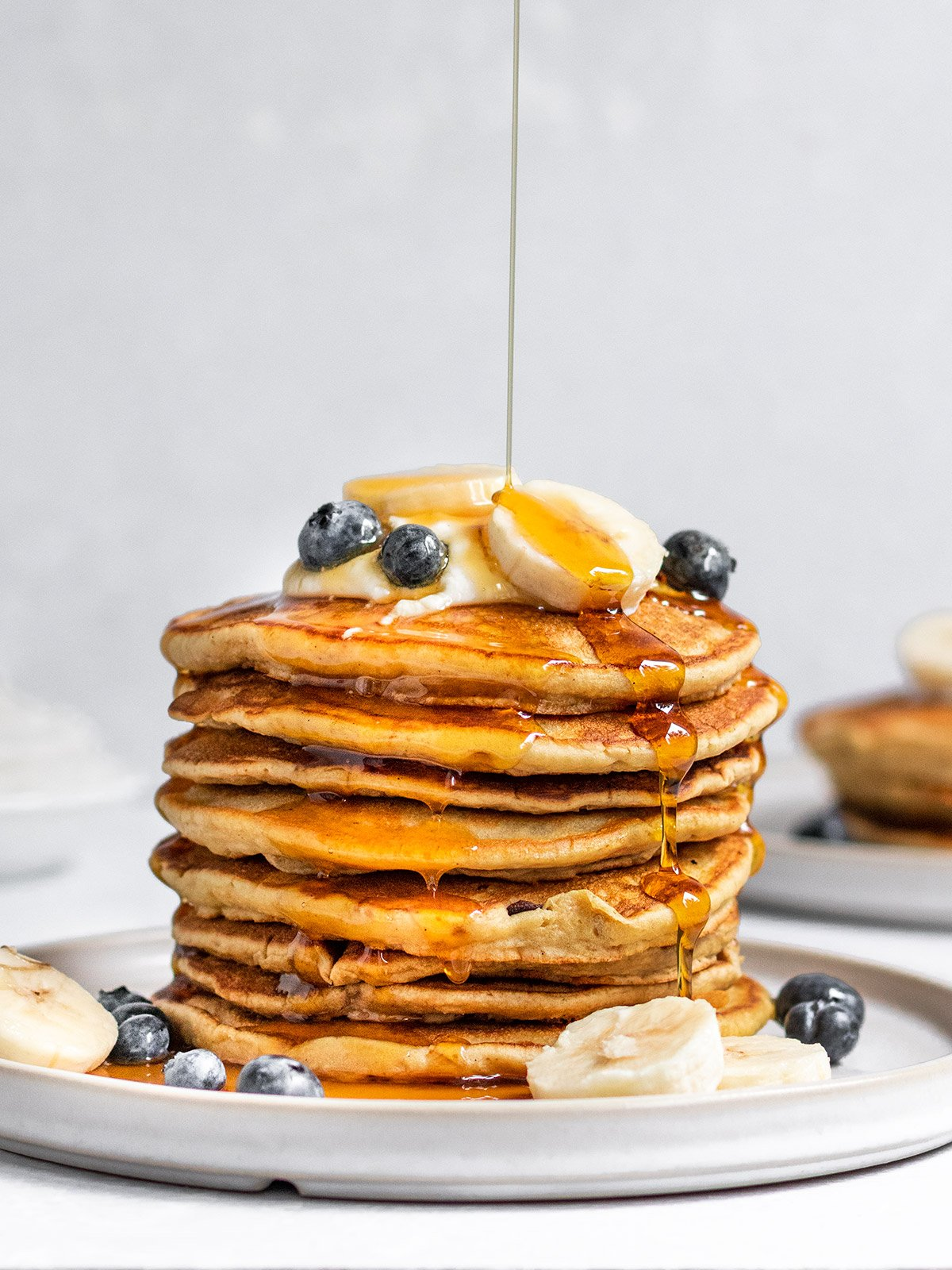 a stack of pancakes with bananas and blueberries getting drizzled with maple syrup