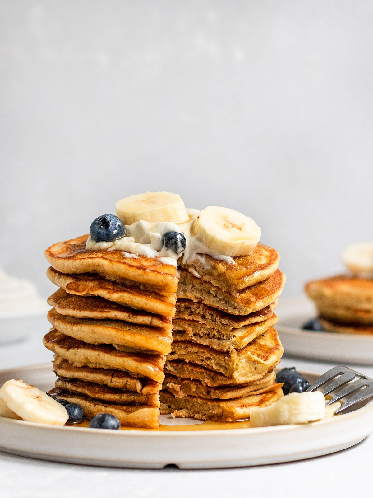 stack of banana pancakes with a slice taken out to show fluffy inside texture