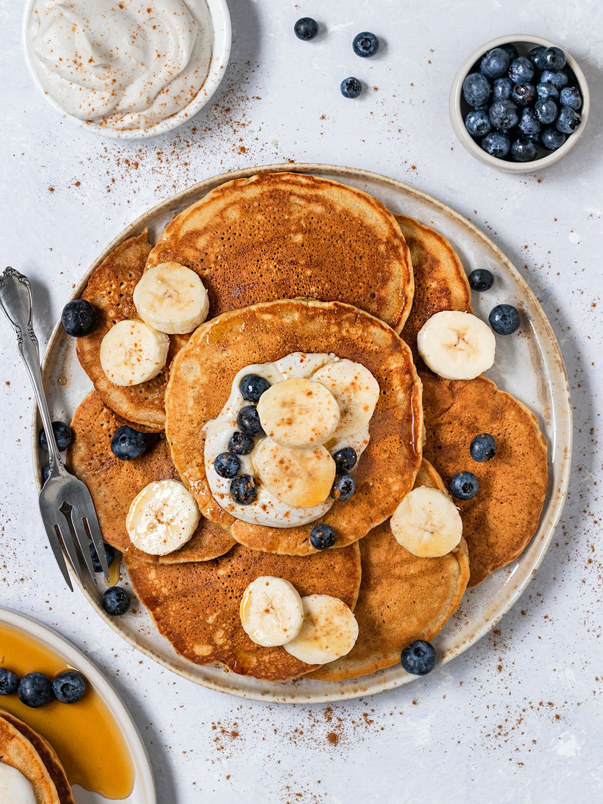 overhead shot of plate of pancakes with bananas, blueberries, coconut cream, and maple syrup on top